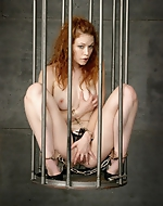 Cage BDSM play. Submissive redhead...